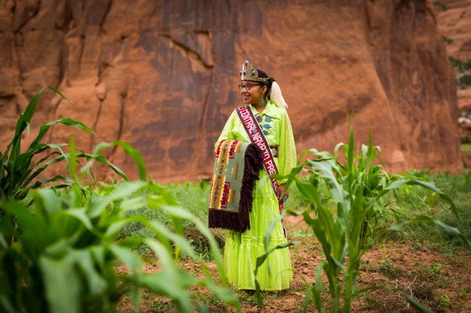 Tonisha Draper stands in her family's corn plot, ed rock behind her. She is wearing a bright green traditional Navajo gown, a crown, and she is holding a fringed Pendleton robe in the Chief Joseph pattern.