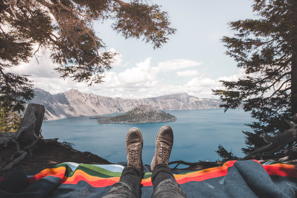 Kyle Houck - a pair of booted feet on a Crater Lake blanket, with the lake ahead.