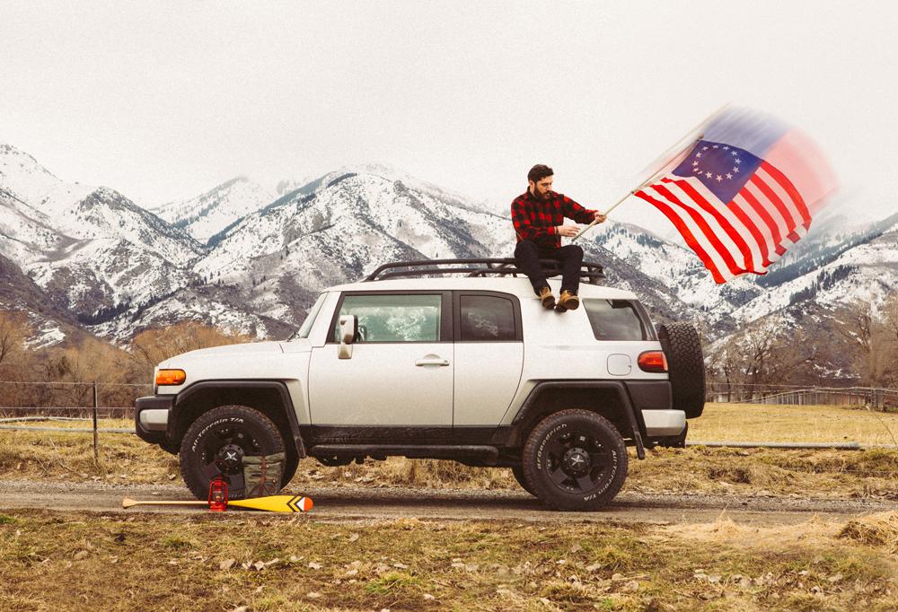 Brandon Burk photogrpahy - a man on a white SUV with an American flag
