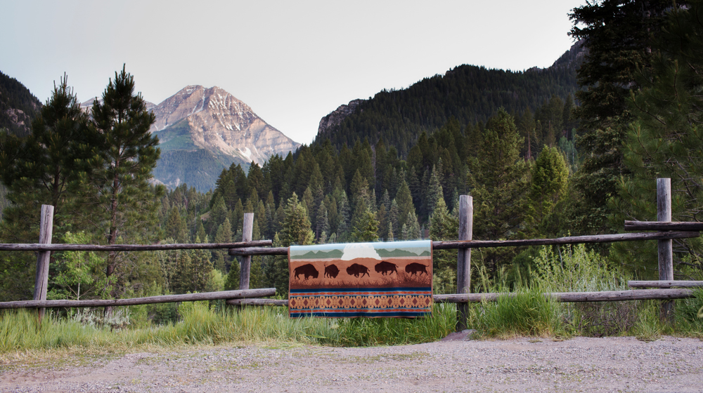 Brandon Burk the Yellowstone Centennial blanket draped over a rail vence, mountain in the background
