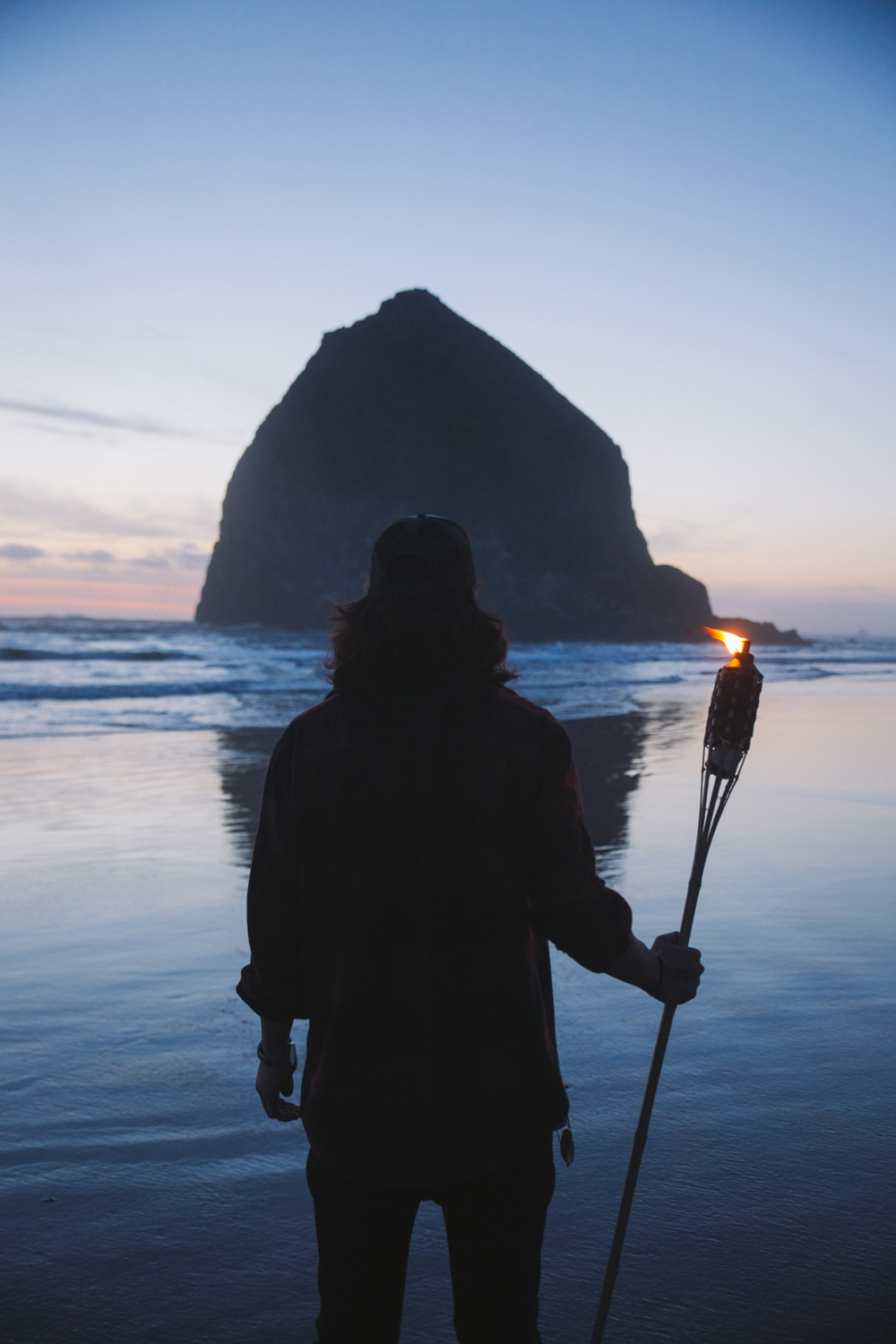 A man in silhouette in front of Haystack Rock