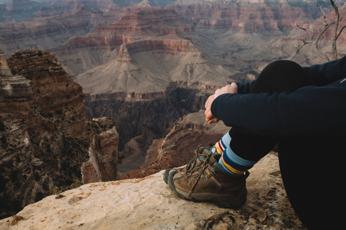 seated woman at rim of Grand Canyon, wearing hiking boots and Pendleton socks.