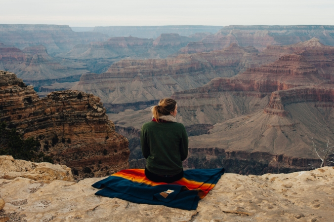woman with ponytail seated on a Pendleton Grand Canyon park blanket overlooking the rim of the Grand Canyon