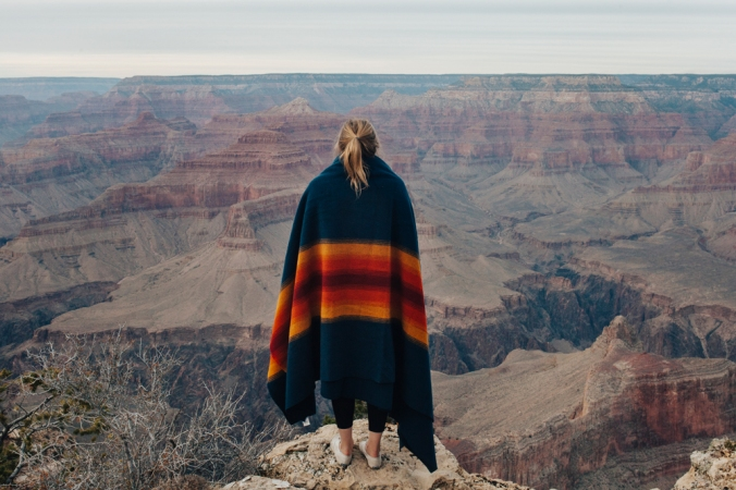woman with ponytail wrapped in Pendleton Grand Canyon blanket stands on the rim of the Grand Canyon