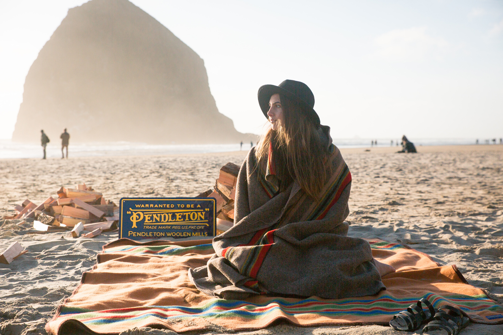 A woman sits on the beach in front of Haystack Rock, wrapped in a Pendleton Camp blanket.