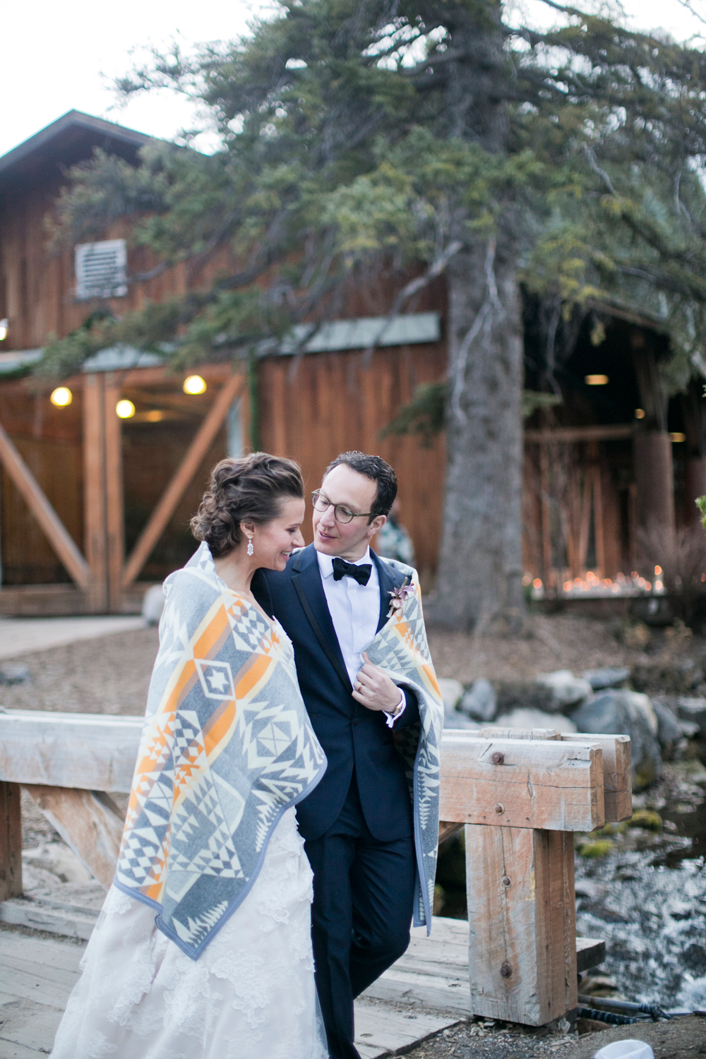 The couple, wrapped in a Pendleton blanket, walks the venue grounds.