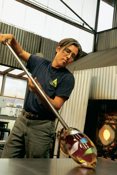 Artist Preston Singletary works a ball of molten glass on a steel tool.