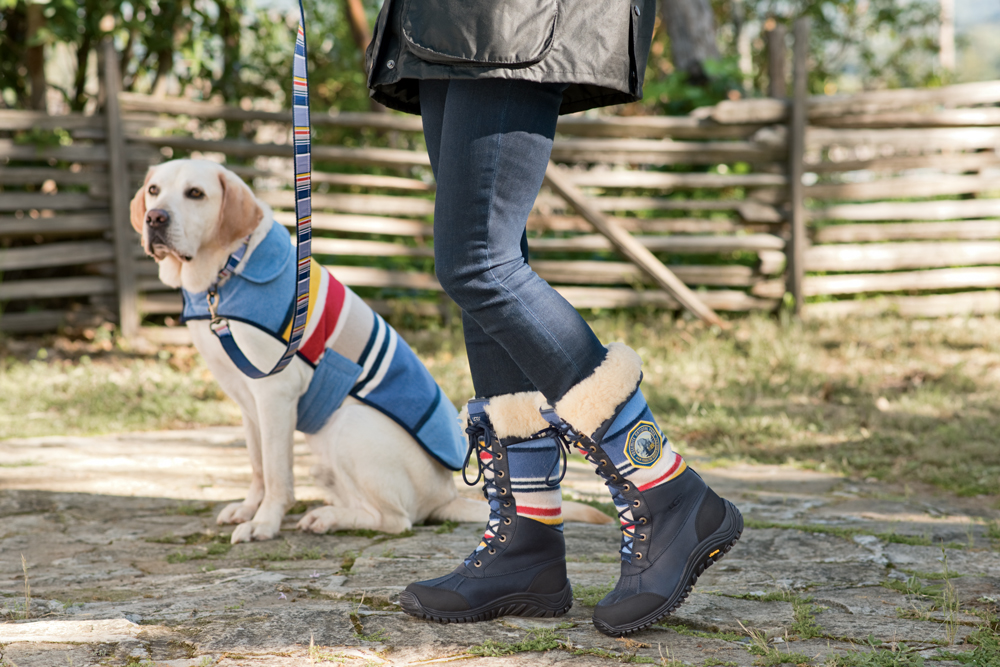 A Yellow Lab in a Pendleton dog coat, walked by a woman wearing Pendleton UGG boots.