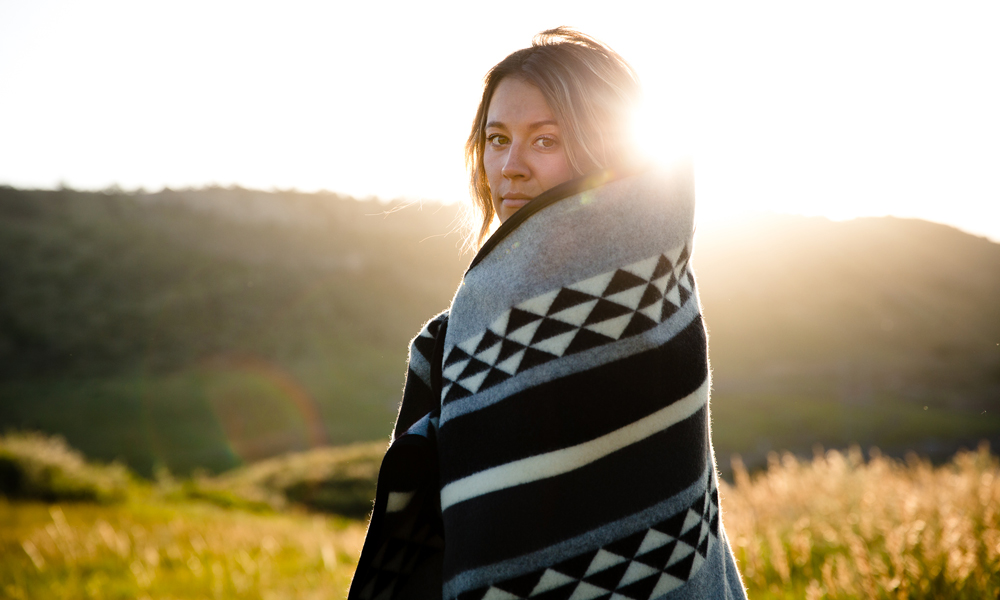 Kate_Rolston shot of a woman standing in a sunlit meadow, wrapped in a blanket.