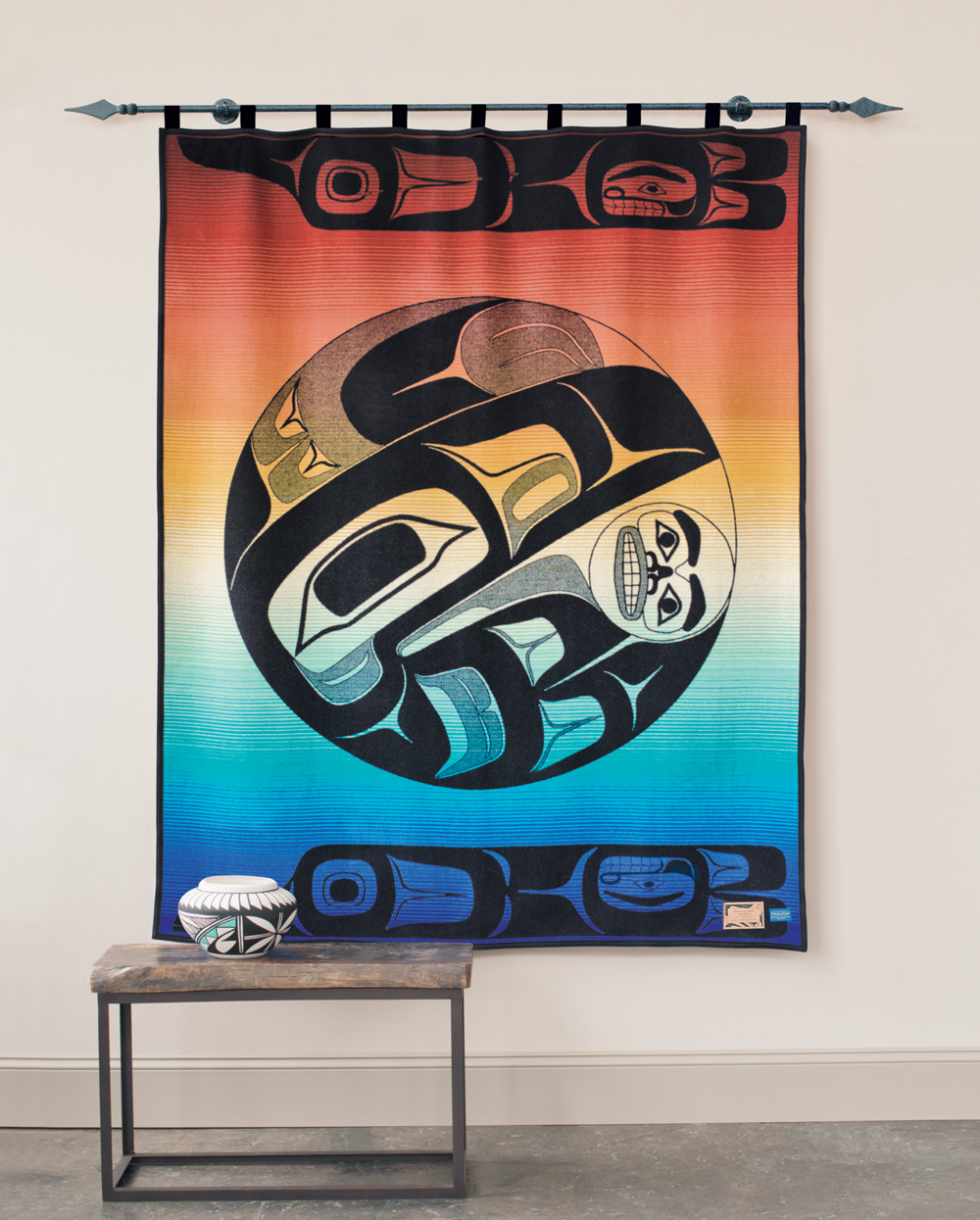 The Pendleton blanket, Raven and the Box of Knowledge, hangs on a wall.