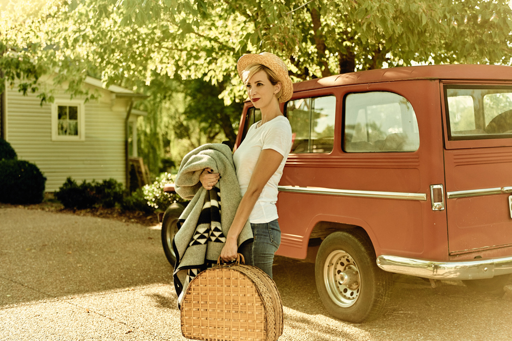 Taylor_Colson_Horton_Cameron_Powell_ a young woman poses by a red vintage vehicle with a basket and blanket