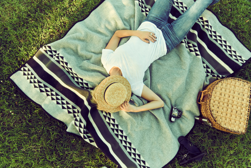 Taylor_Colson_Horton_Cameron_Powell_ A woman with a hat over her face relaxes on a Yosemite Blanket