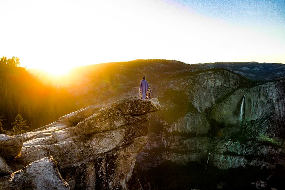 A woman wrapped in a blanket stands looking at the Yosemite landscape - photo by Allie Taylor