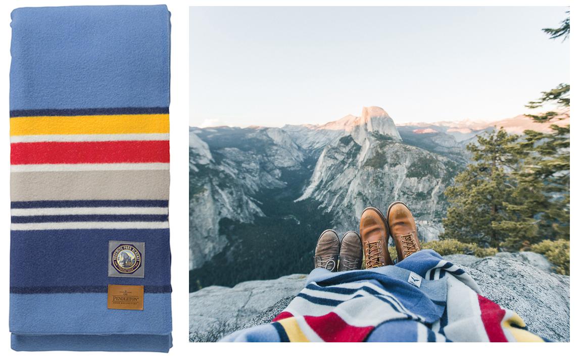 Yosemite park blanket, folded, next to a couple enjoying a mountaintop view of Yosemite