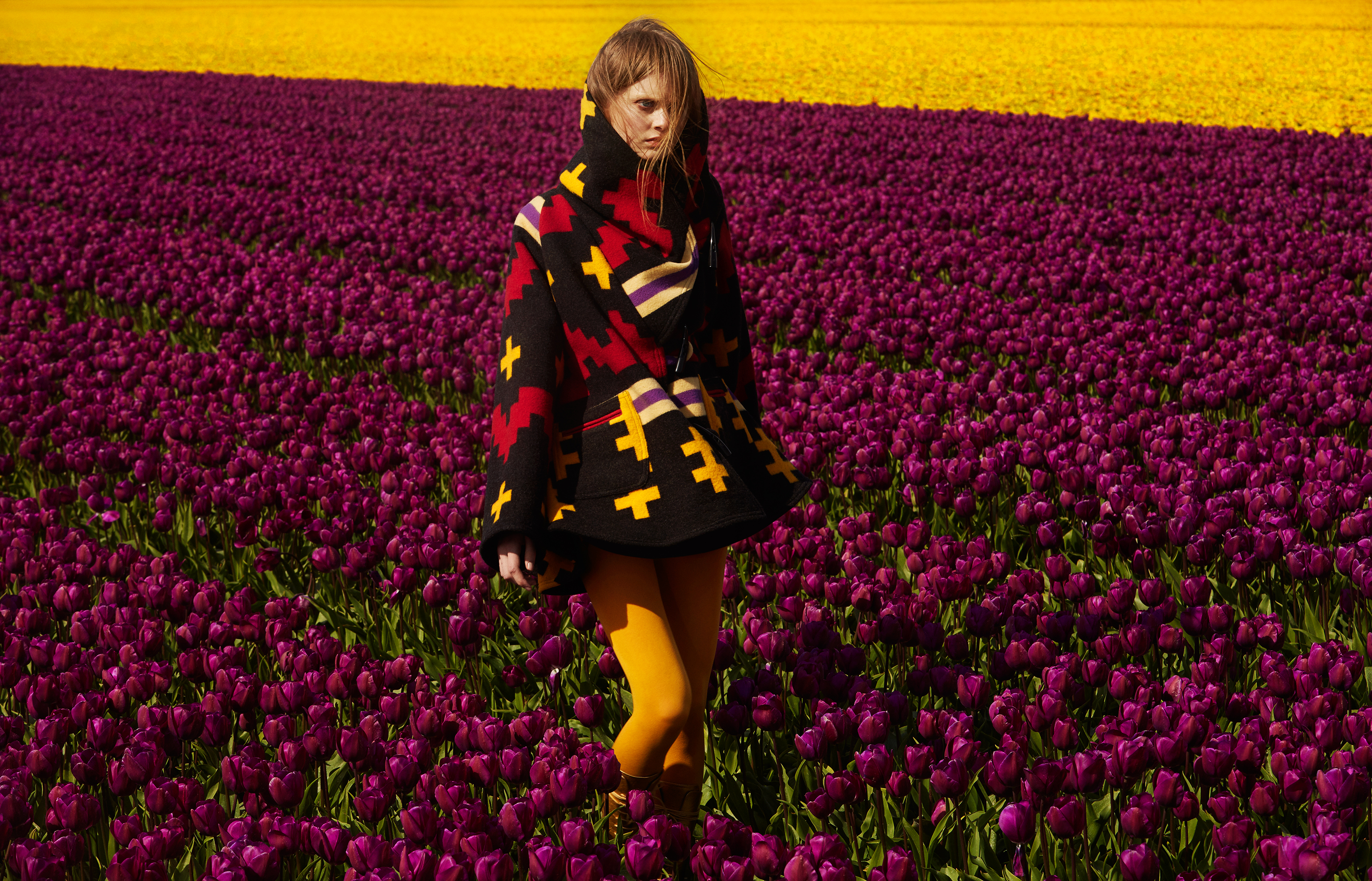 A model wearing a cape stand in a field of purple tulips.