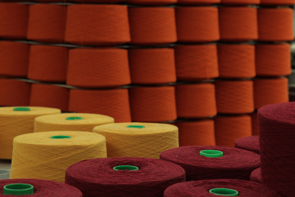 brightly colored spools of spun wool wait to be threaded onto a loom