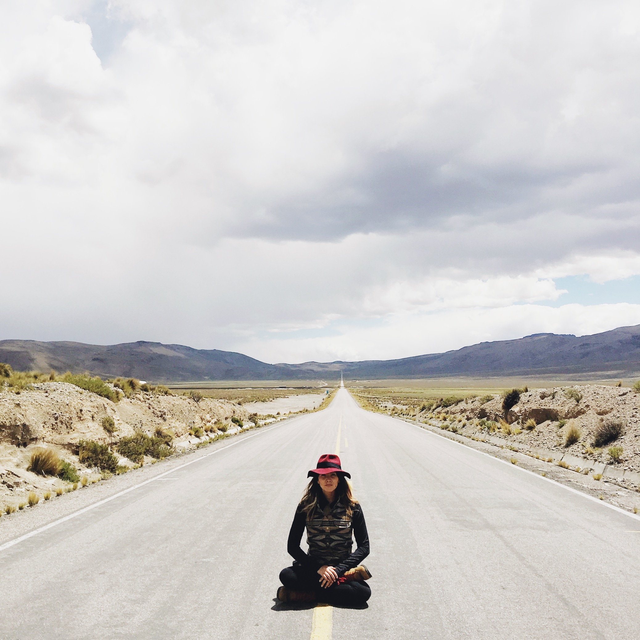 A woman sits crosslegged on a highway, with the road receding into the far distance.