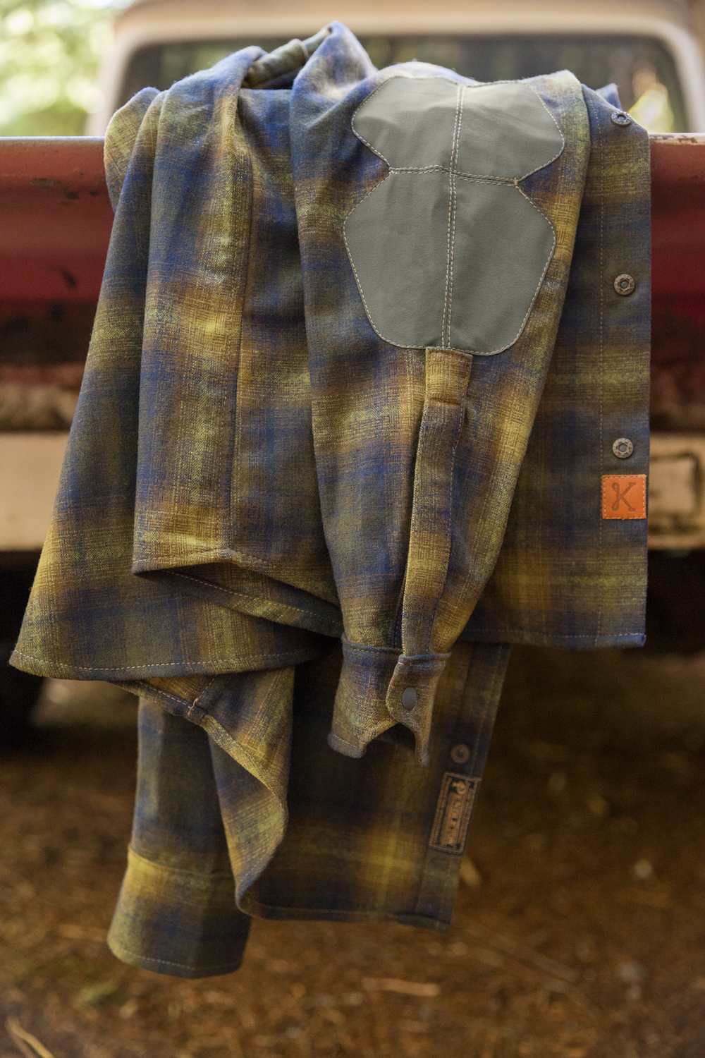 a Pendleton Kitsbow shirt draped over the side of a vintage pickup truck