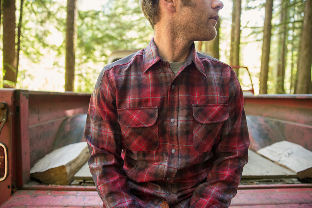 a man sits on the tailgate of a vintage pickup truck, wearing a Pendleton Kitsbow shirt
