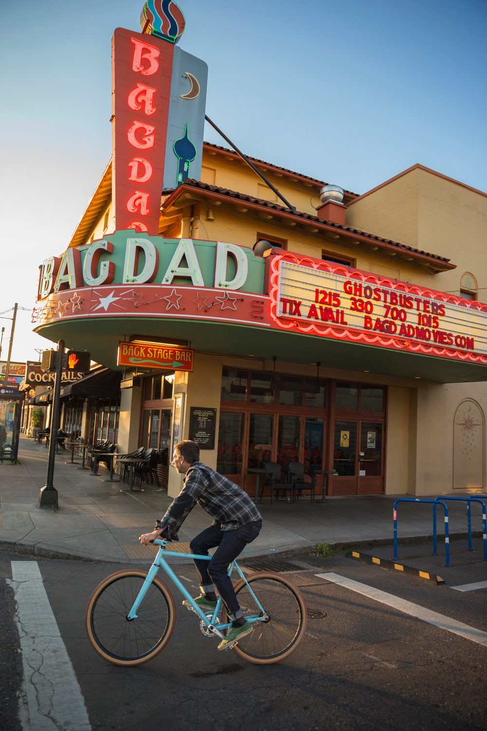 man riding bike in front of Portland's Baghdad movie theater