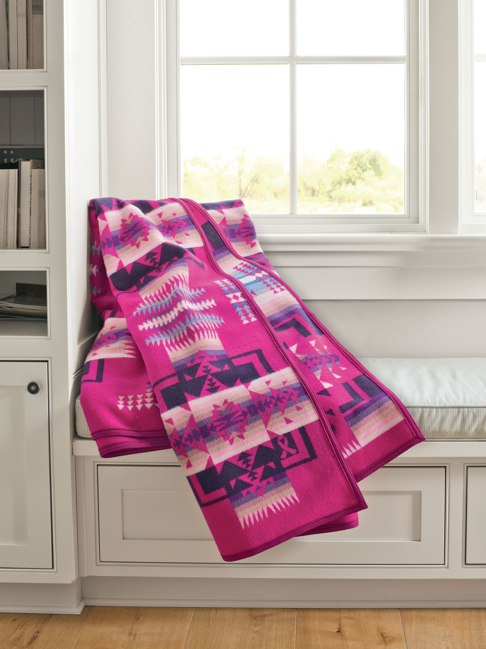 A cherry-pink Chief Joseph blanket, folded and draped on a windowseat. This special blanket benefits the Native American women's clinic at NARA.