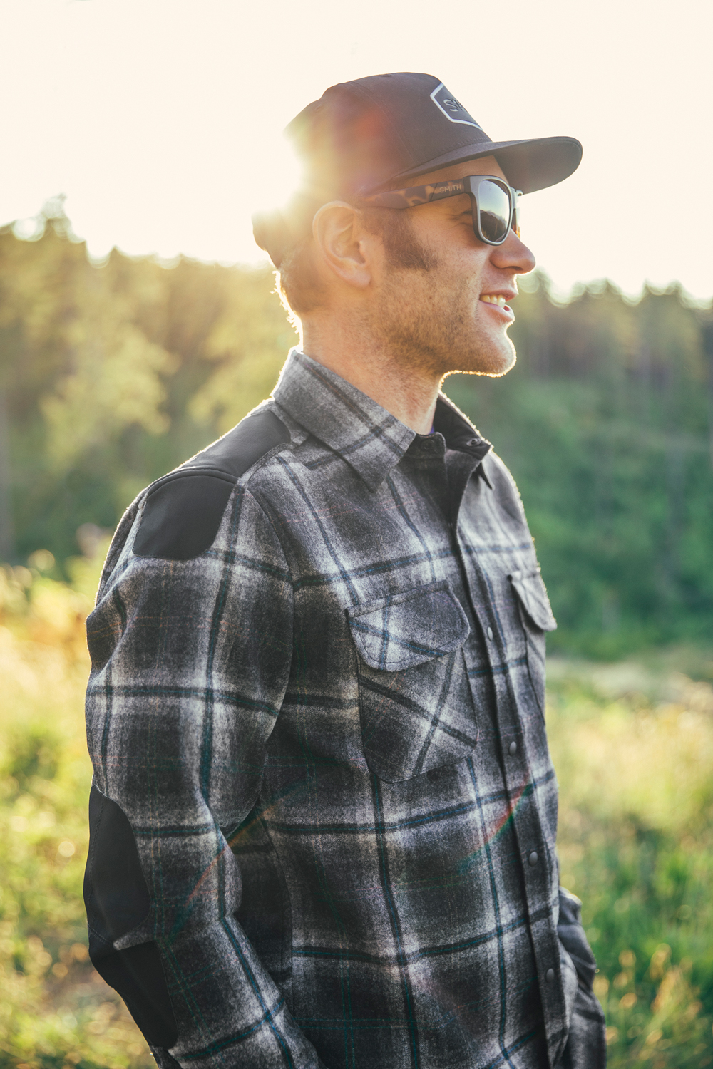A man in a plaid shirt stands in the forest