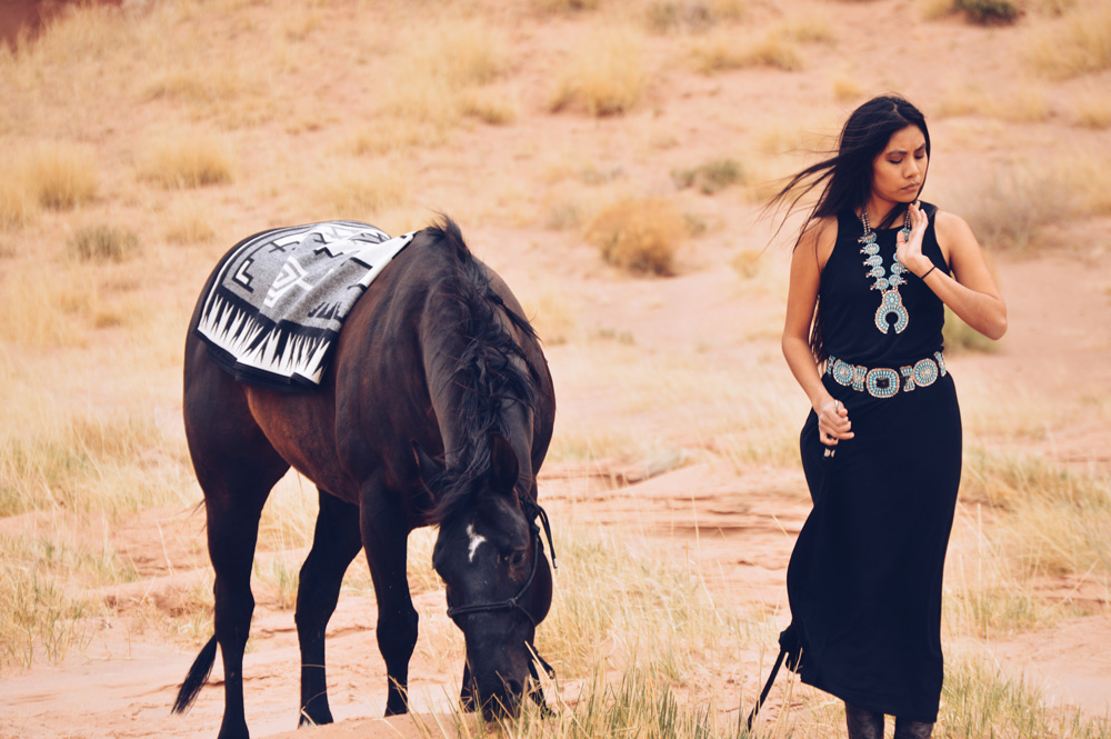 Shondina Lee Yikasbaa leads horse draped with Naskan saddle blanket
