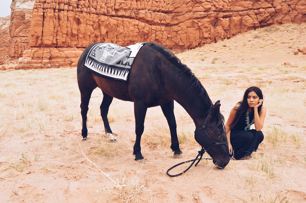 Shondina Lee Yikasbaa kneels hnear a horse draped with Naskan saddle blanket