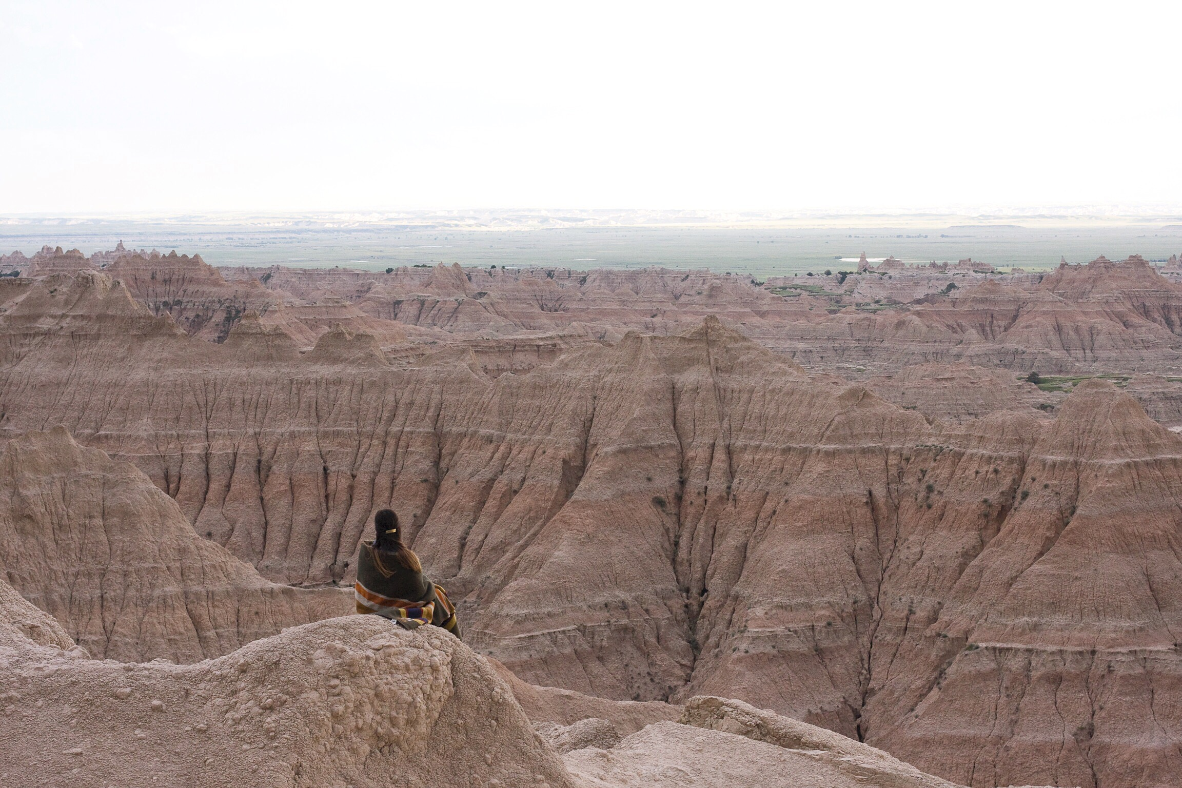 A woman wrapped in a Pendleton blanket looks at Badlands National Park - photo by emmanuel_beltran