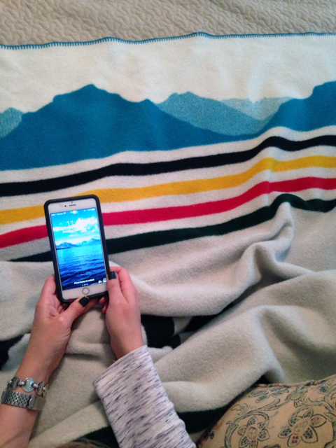 hands hold a cell phone showing a photo of Glacier National park, next to the silhouette of the glaciers on a Pendleton blanket.