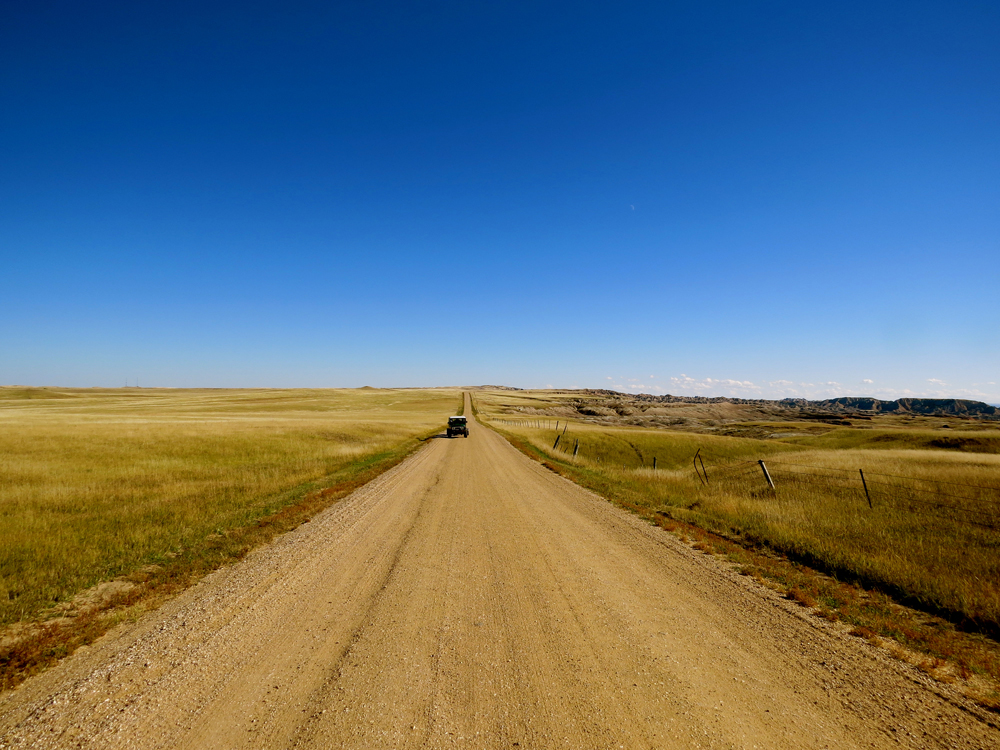 A dirt road in South Dakota, with a vehicle in the distance.
