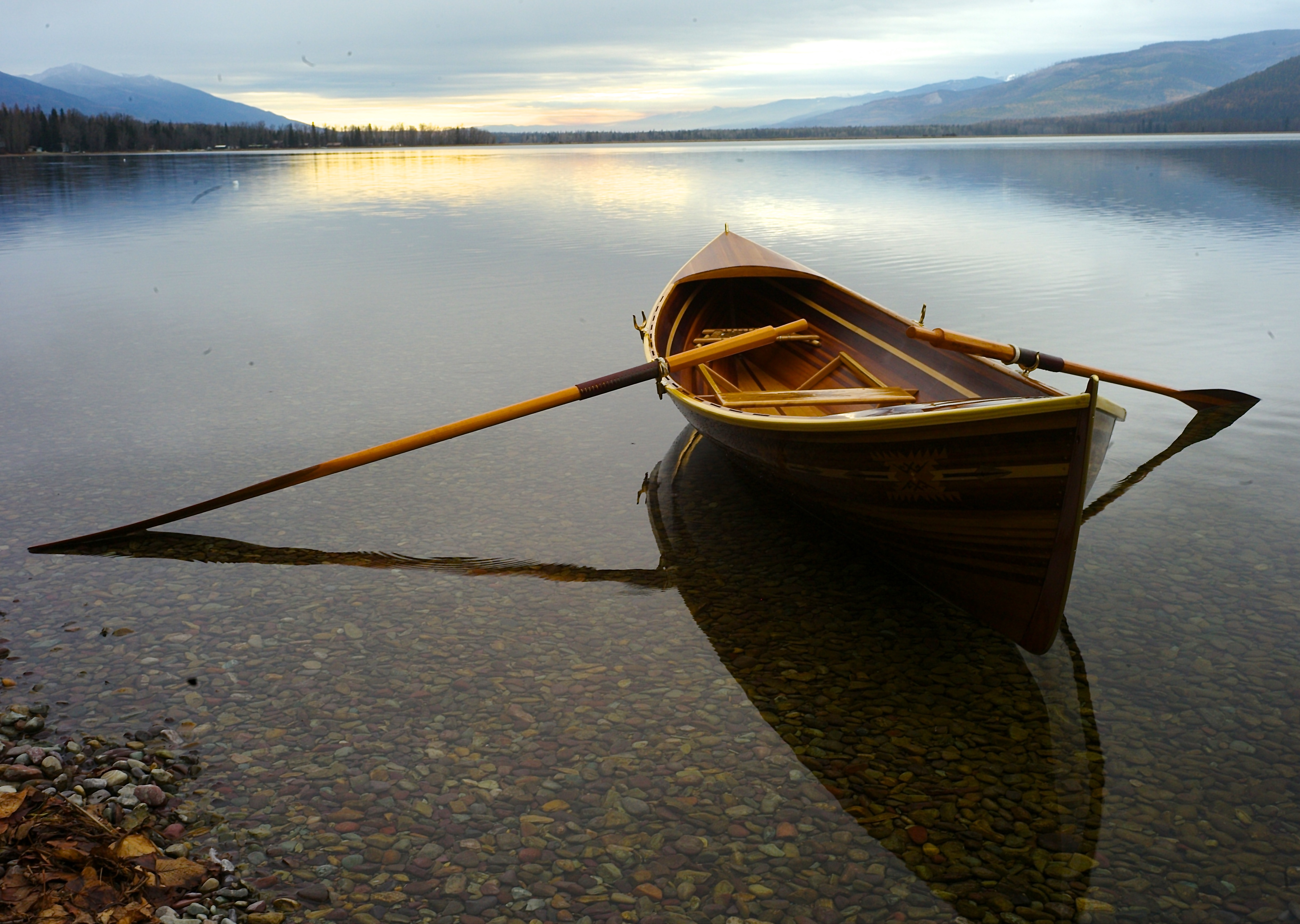 CANOE AND OARS AT THE SHORE OF A LAKE