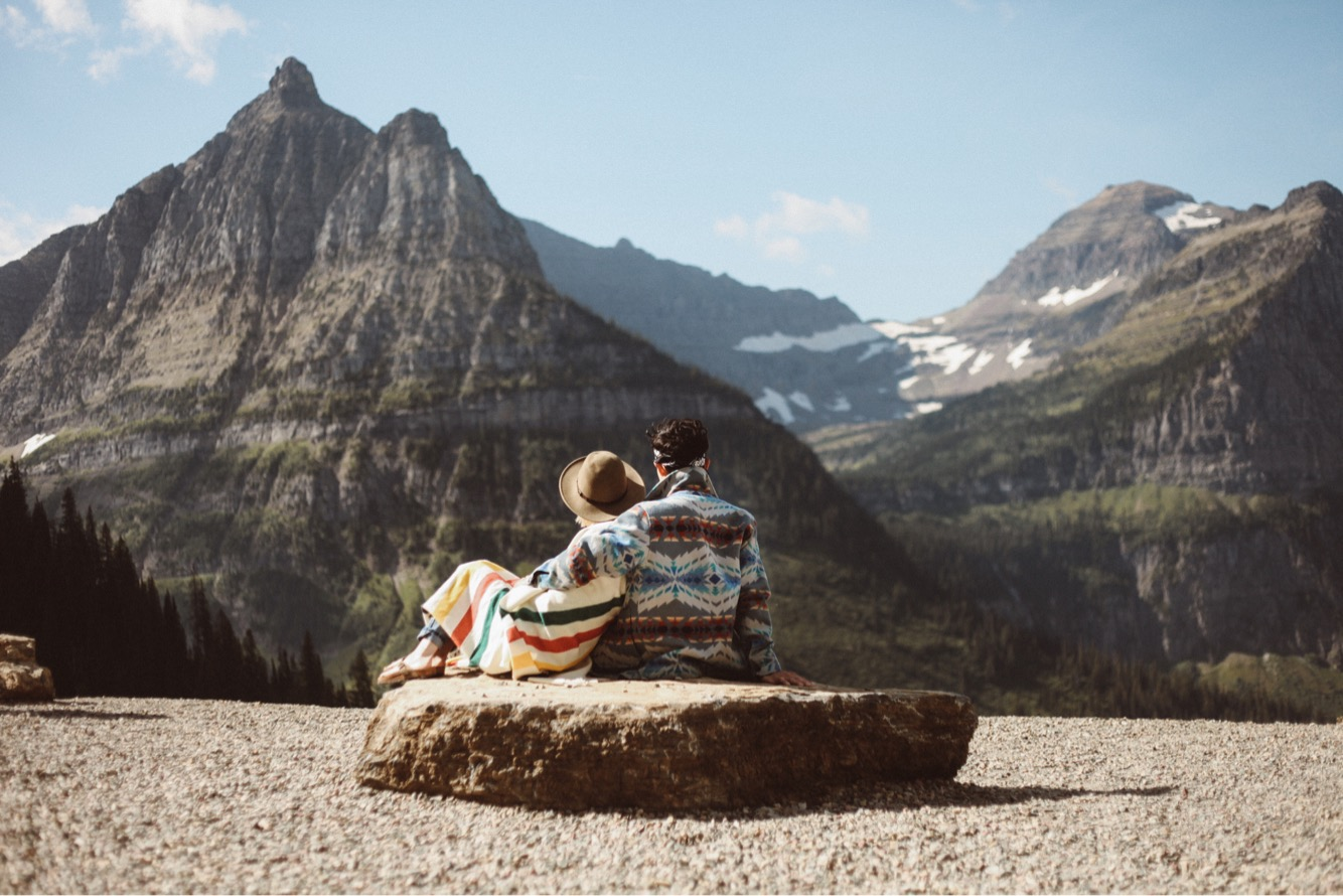 A man and woman sit on a boulder at Glacier National park