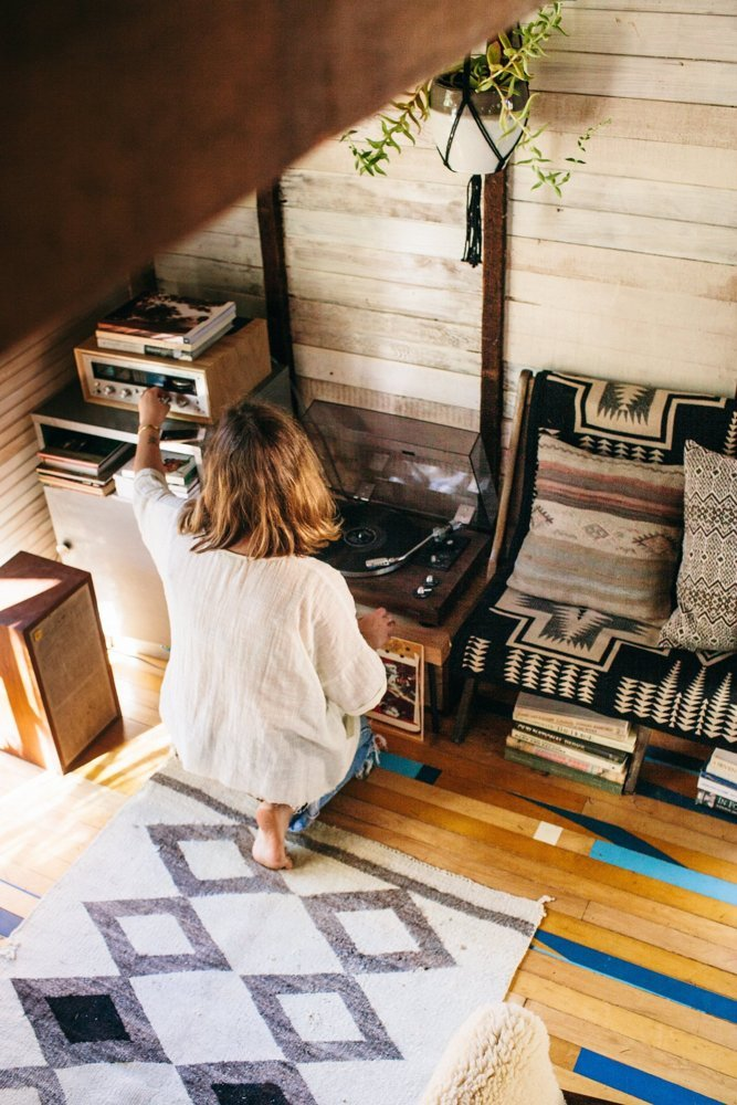 A woman adjusts the sound on a stereo in her tiny home.