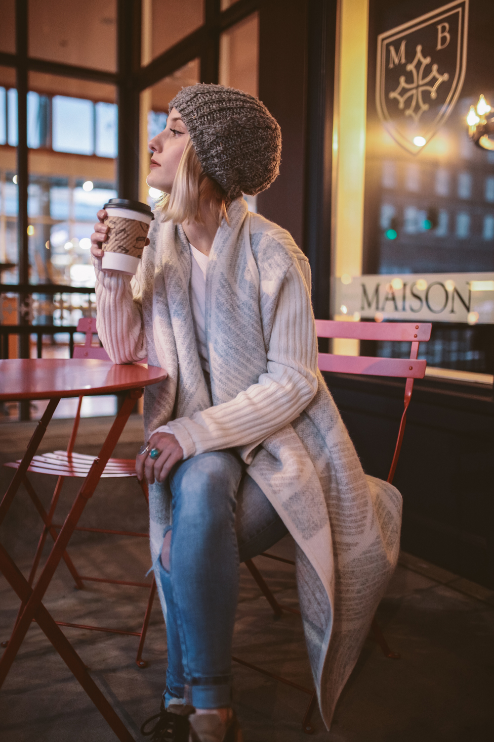 mikal_wright: a young woman enjoys her coffee in a coffee shop