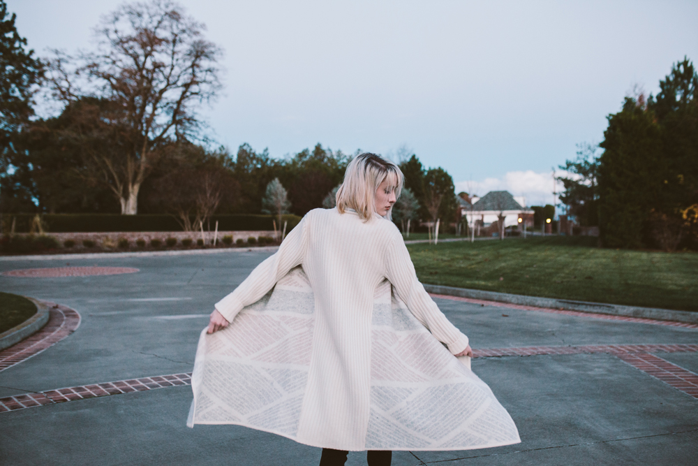 mikal_wright: a woman stands on a pavilion, her sweater twirling around her
