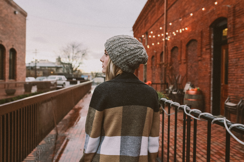 mikal_wright: a woman in a sweater and knit cap stands by a brick warehouse