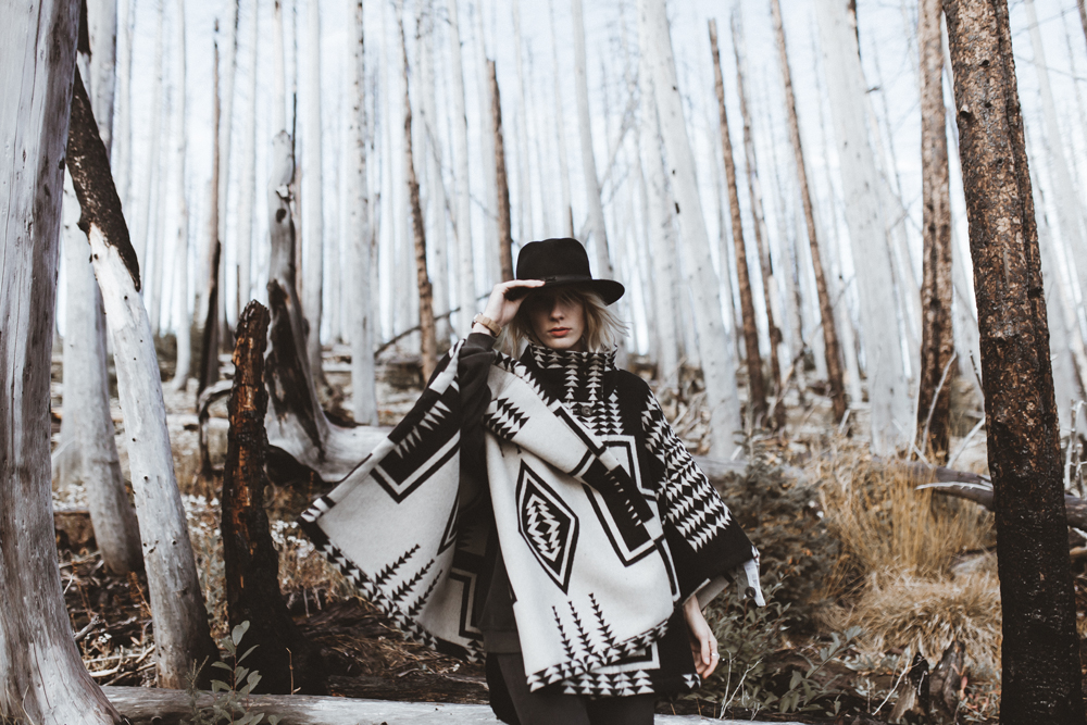 mikal_wright: a woman in a black and white Pendleton cape stands in a forest