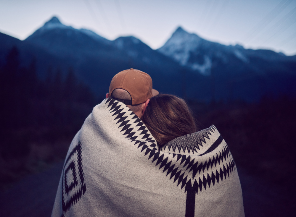 Sean and Tam look at the mountains while wrapped in a Pendleton blanket
