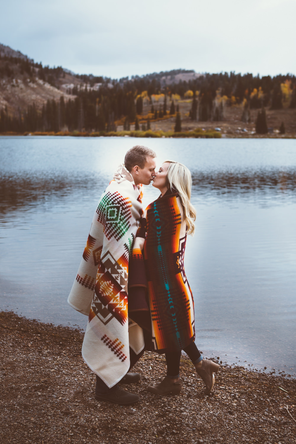A couple kisses by a lake, wrapped in blankets.