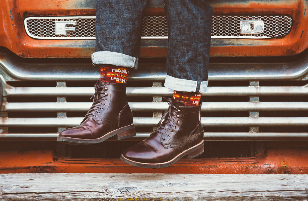 Brandon-Burk-Photography: a photo of a man's feet in boots and Pendleton socks, in front of a car grill.