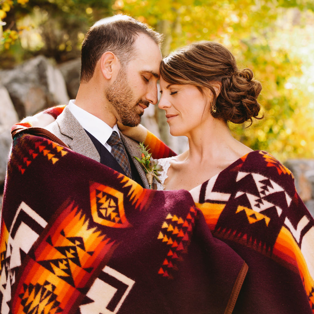 A couple embraces in their wedding attire, wrapped in a Pendleton Chief Joseph blanket