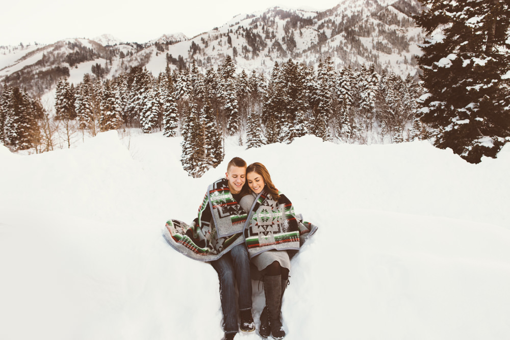 A couple in the snow, wrapped in a blanket