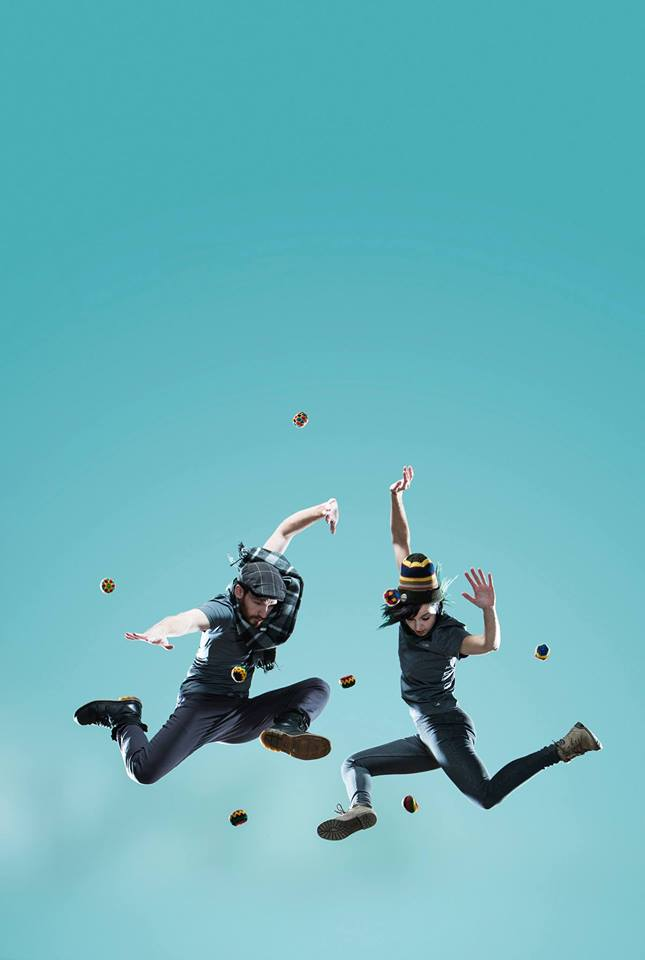 Two BodyVox dancers leap in the air surrounded by hackysacks.