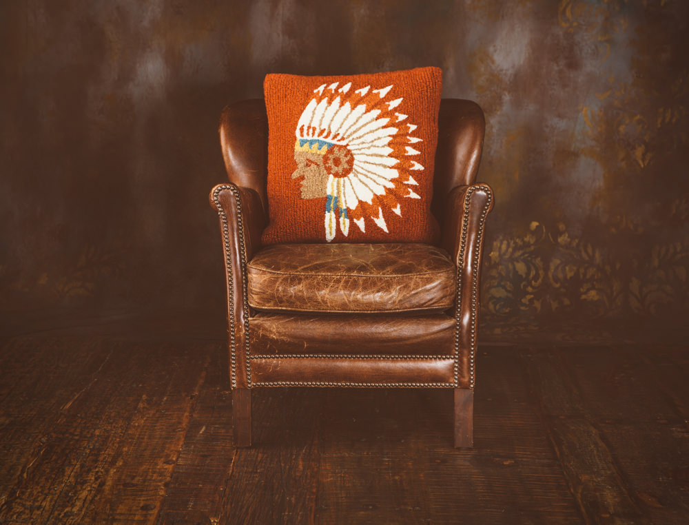 A leather chair and hooked wool pillow by BrandonBurkPhotography.com