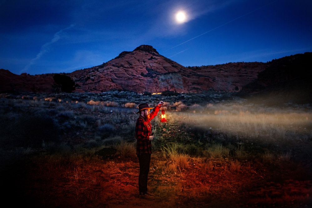 BrandonBurkPhotography.com A man poses with a lantern in the Utah desert at night.