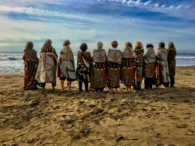 Final Ceremony: eleven women wrapped in Basket Dance blankets stand in a line at the beach.