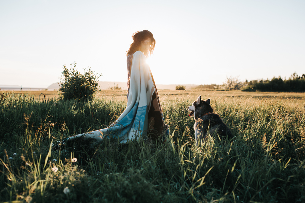 A young woman and a husky dog stand ni a field of tall grass.