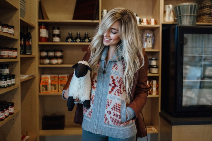 A woman stands in a shop holding a toy stuffed lamb.