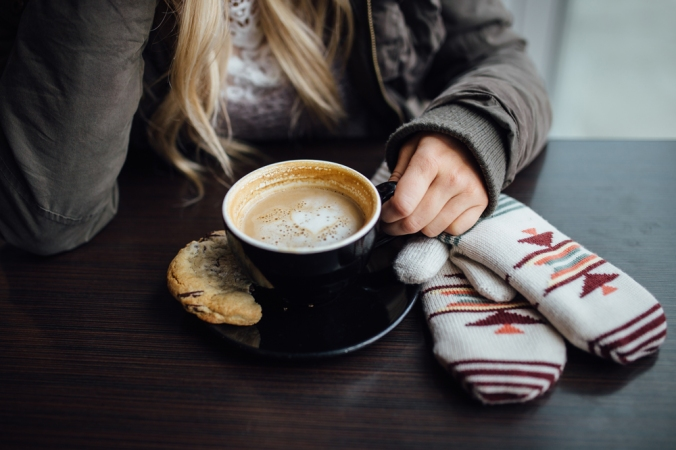 A woman sits at a table with a latte and a pair of mittens.